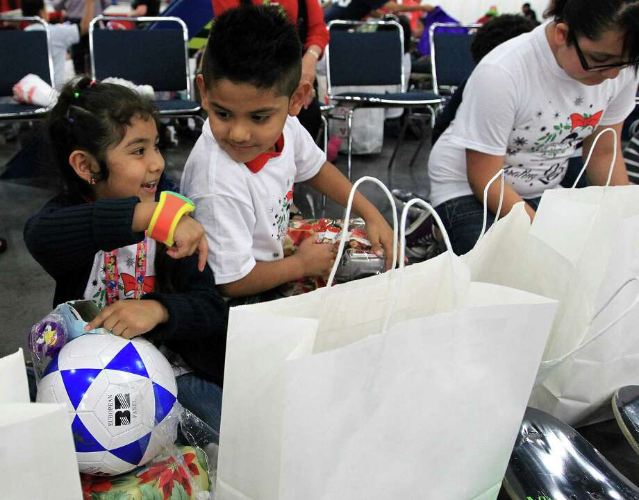 Annaelizabeth Uriostegui, 6, shows her brother Jorge Uriostegui, 7, a watch as she opens her presents with the Jensen Elementary School students from Pasadena during the 25th annual Navidad en el Barrio at the George R. Brown Convention Center, Saturday, Dec. 15, 2012, in Houston. Photo: Karen Warren, Houston Chronicle / © 2012 Houston Chronicle