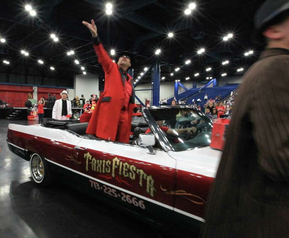 Pancho Claus rides in his Taxis Fiesta car during the 25th annual Navidad en el Barrio at the George R. Brown Convention Center. Photo: Karen Warren, Houston Chronicle / © 2012 Houston Chronicle