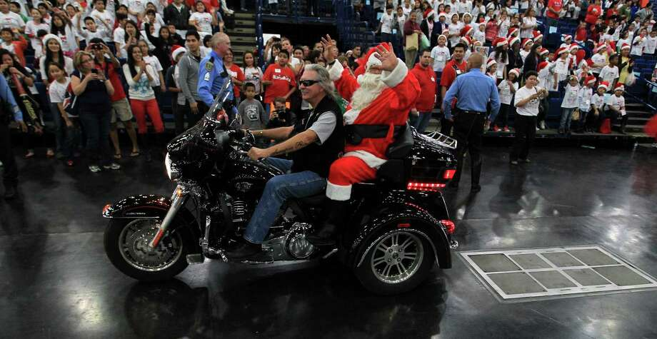 Santa Claus rides into the room on a motorcycle during the 25th annual Navidad en el Barrio at the George R. Brown Convention Center. Photo: Karen Warren, Houston Chronicle / © 2012 Houston Chronicle