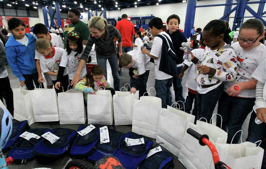 Students from Jensen Elementary School look for their names on backpacks during the 25th annual Navidad en el Barrio at the George R. Brown Convention Center. Photo: Karen Warren, Houston Chronicle / © 2012 Houston Chronicle