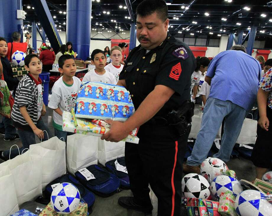 Students from Jensen Elementary School get presents from Pasadena Police Sgt. John Bangilan during the 25th annual Navidad en el Barrio at the George R. Brown Convention. Photo: Karen Warren, Houston Chronicle / © 2012 Houston Chronicle