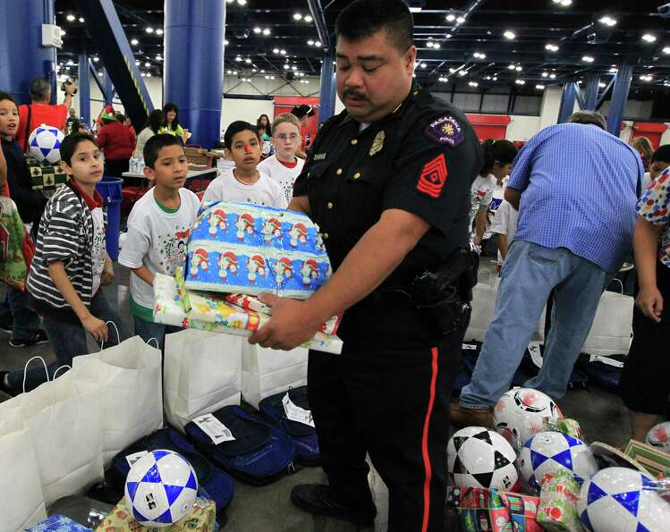 Students from Jensen Elementary School get presents from Pasadena Police Sgt. John Bangilan during t