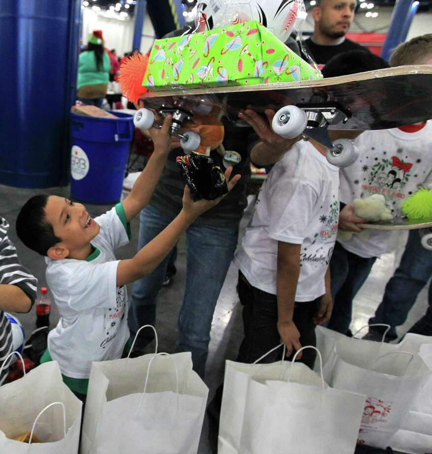 Students from Jensen Elementary School including Jose Gonzalez, 9, right, get presents from Pasadena Police Sgt. John Bangilan during the 25th annual Navidad en el Barrio. Photo: Karen Warren, Houston Chronicle / © 2012 Houston Chronicle