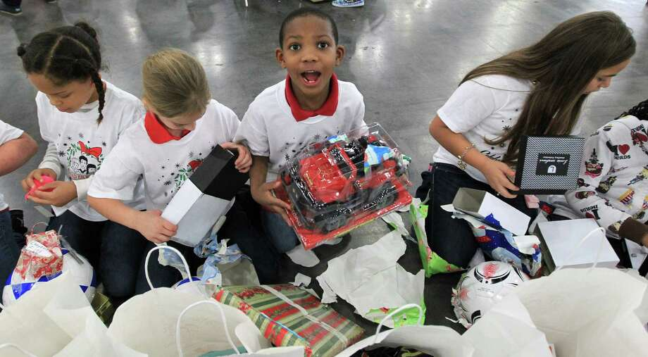 Jayvion Durden,7, of Jensen Elementary School in Pasadena, reacts after opening up his presents during the 25th annual Navidad en el Barrio. Photo: Karen Warren, Houston Chronicle / © 2012 Houston Chronicle