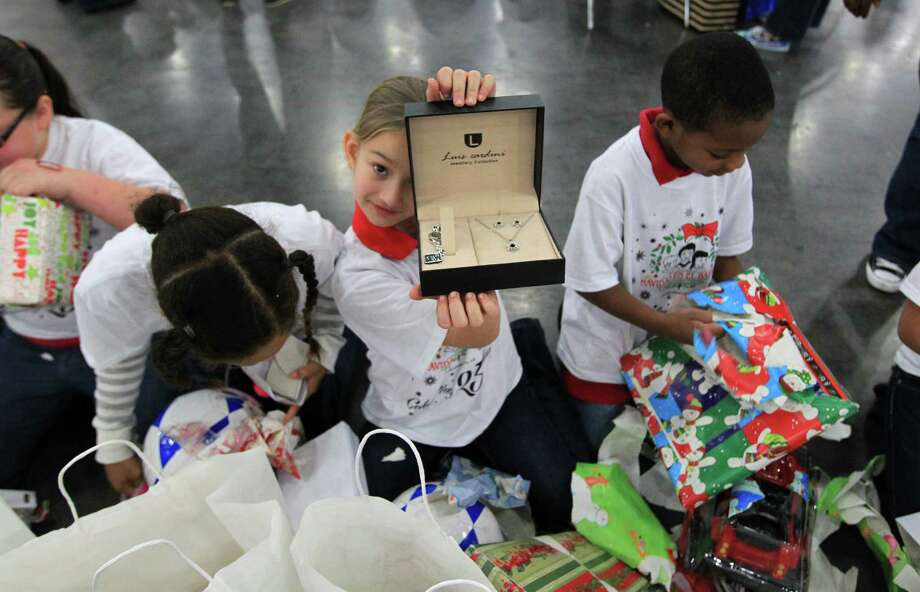 Jessica Chesik, 8,  of Jensen Elementary School in Pasadena, reacts after opening up her presents during the 25th annual Navidad en el Barrio. Photo: Karen Warren, Houston Chronicle / © 2012 Houston Chronicle