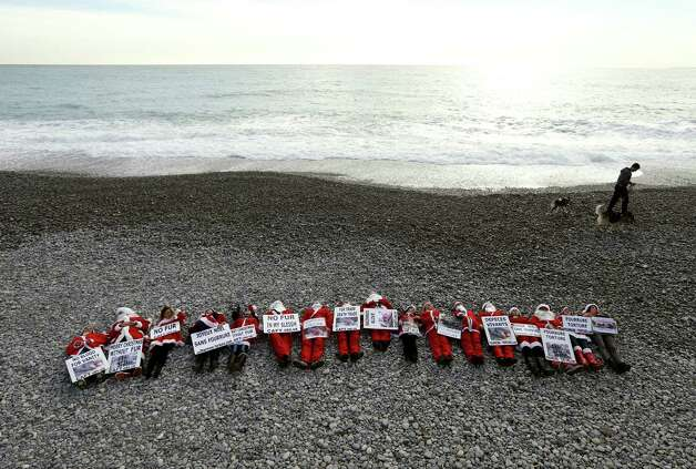 """Members of the French anti-fur group """"CAFT"""" (The Coalition to Abolish the Fur Trade), dressed up as Santa Claus demonstrate on a beach to denounce the """"horror and suffering that is hidden behind the glamor of fur"""", on December 15, 2012, in Nice, southeastern France. Photo: VALERY HACHE, AFP/Getty Images / AFP"""