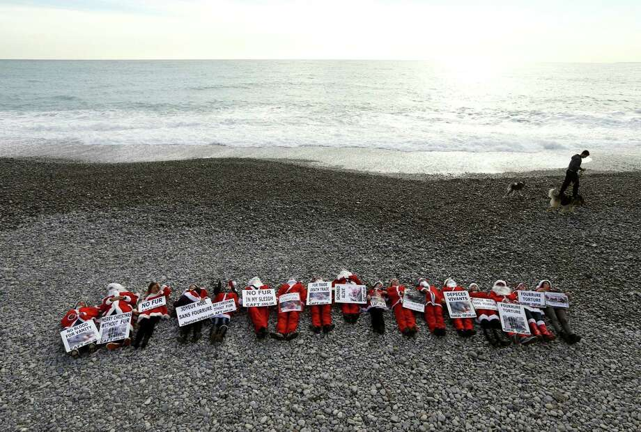 "Members of the French anti-fur group ""CAFT"" (The Coalition to Abolish the Fur Trade), dressed up as Santa Claus demonstrate on a beach to denounce the ""horror and suffering that is hidden behind the glamor of fur"", on December 15, 2012, in Nice, southeastern France. Photo: VALERY HACHE, AFP/Getty Images / AFP"