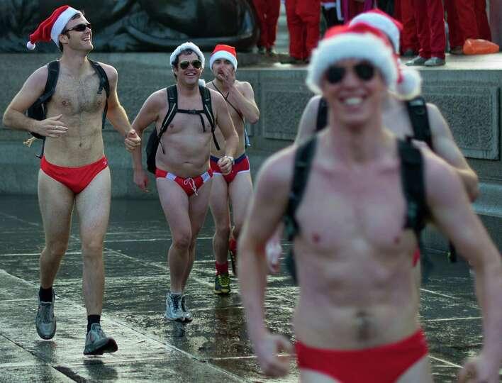 Revellers wearing bathing suits and Santa hats take part in 'Santacon' run through Trafalgar Square