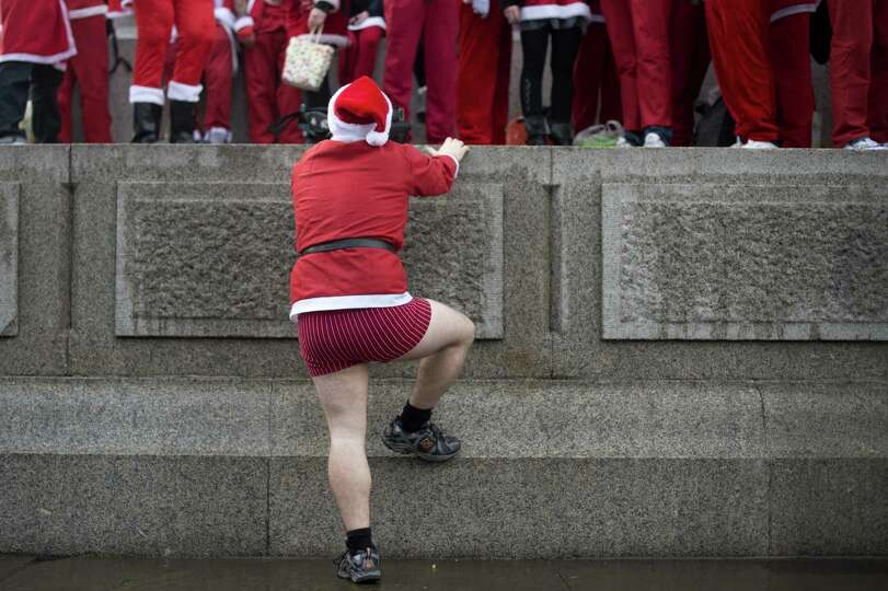 A reveller in a santa costume attempts to climb up onto Nelson's Column during a 'Santacon' run thro