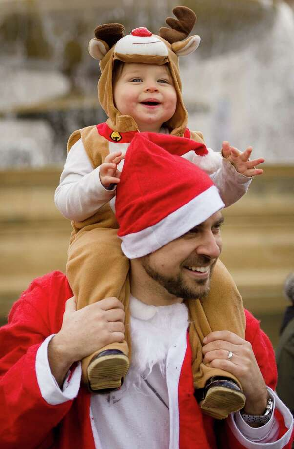 "A young child in a reindeer costume joins hundreds of ""Santas"" during a 'Santacon' in Trafalgar Square in central London on December 15, 2012, less than two weeks before Christmas. Photo: LEON NEAL, AFP/Getty Images / AFP"