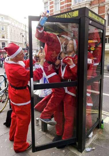 Revellers in Santa costumes jam into a telephone box during a 'Santacon' near Trafalgar Square in ce