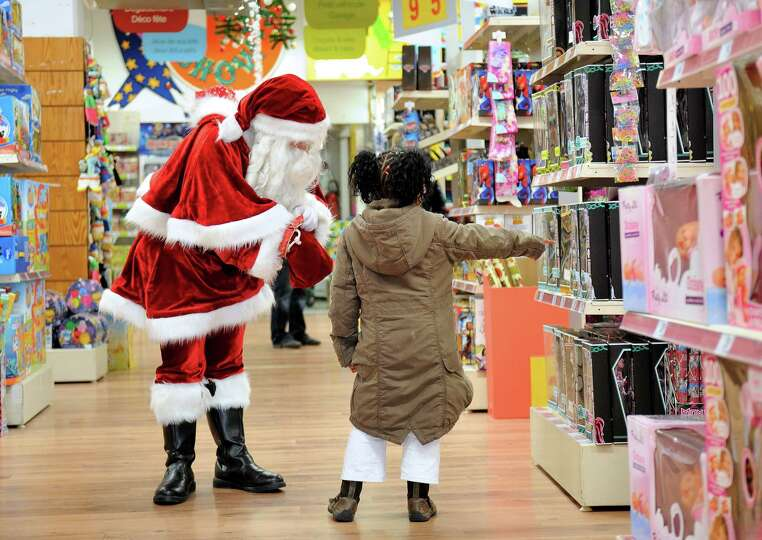 A little girl indicates to Santa Claus a toy, on December 15, 2012 in a toy store in Lille, northern