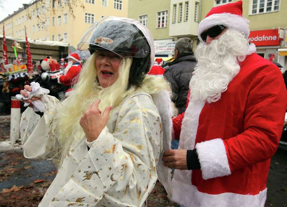 "Bikers disguised as angel and Santa Claus prepare to ride a bike during the bike tour ""Santa Claus on Road"" in Berlin, on December 15, 2012 in Berlin. The bikers charity event takes place for the 15th time. Photo: WOLFGANG KUMM, AFP/Getty Images / DPA"