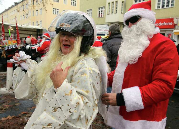 Bikers disguised as angel and Santa Claus prepare to ride a bike during the bike tour