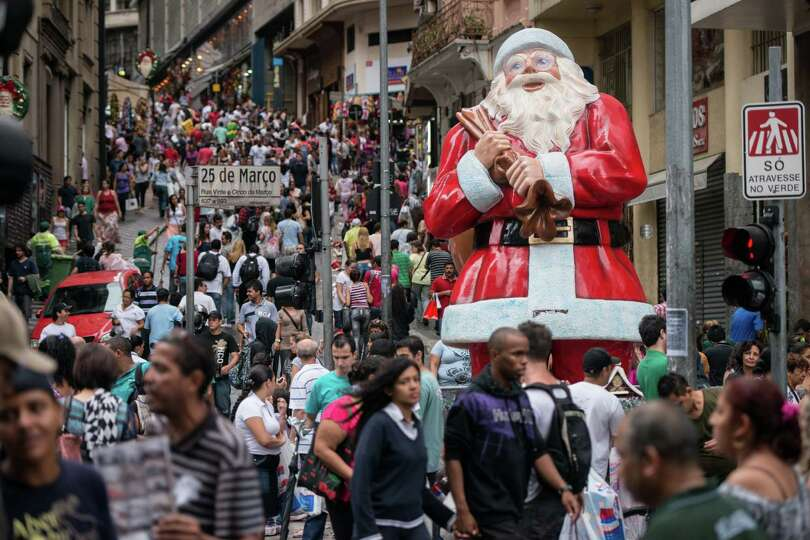 People walk past a statue of Santa Claus placed at
