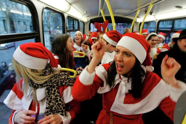 Revellers dressed up in Santa outfits travel on a bus in London during a Santacon festival parade through the streets of London, Saturday, Dec. 15, 2012. Photo: Sang Tan, Associated Press / AP