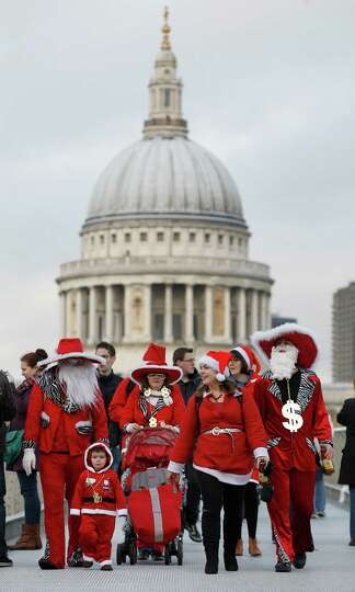 Backdropped by St Paul's Cathedral revellers dressed up in Santa outfits pose as they walk across th