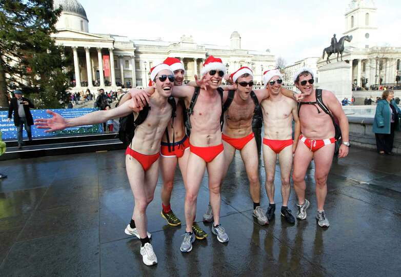 Revellers dressed up in Santa hats pose as hundreds gather at Trafalgar Square in London during a Sa