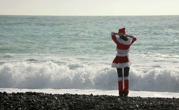Activist dressed in Santa Claus costume from the coalition to abolish the fur trade, stands on the beach of Nice during a demonstration with signs showing animals skinned alive on the beach in Nice, southern France, Saturday, Dec. 15, 2012. Activists exhort shoppers not buy fur for Christmas. Photo: Lionel Cironneau, Associated Press / AP