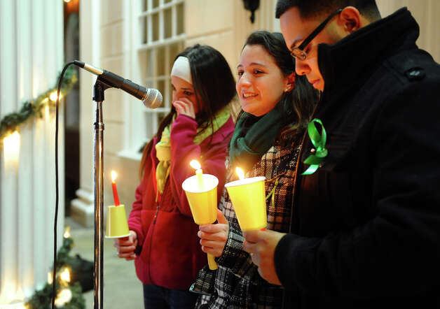 Jillian Soto, center, thanks the hundreds of people who came out to attend a candlelight vigil in memory of victims from yesterday's mass shooting in Newtown, which was held behind Stratford High School on the Town Hall Green in Stratford, Conn. on Saturday December 15, 2012. Jillian's sister Vicki, a Stratford native, was a teacher at Sandy Hook Elementary School and was one of the victims in the shooting. At left is sister Carly Soto and family friend Louis Sanchez. Photo: Christian Abraham / Connecticut Post