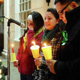 Jillian Soto, center, thanks the hundreds of people who came out to attend a candlelight vigil in memory of victims from yesterday's mass shooting in Newtown, which was held behind Stratford High School on the Town Hall Green in Stratford, Conn. on Saturday December 15, 2012. Jillian's sister Vicki, a Stratford native, was a teacher at Sandy Hook Elementary School and was one of the victims in the shooting. At left is sister Carly Soto and family friend Louis Sanchez.