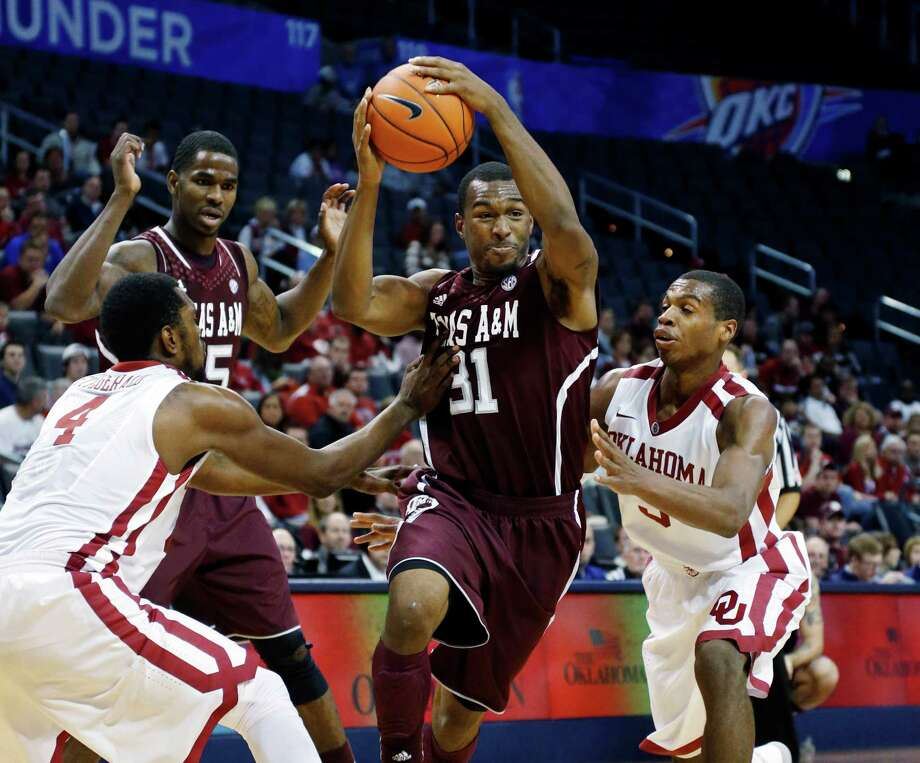Texas A&M guard Elston Turner (31) drives between Oklahoma forward Andrew Fitzgerald (4) and guard Buddy Hield (3) in the first half of an NCAA college basketball game in the All College Classic tournament in Oklahoma City, Saturday, Dec. 15, 2012. Oklahoma won 64-54. (AP Photo/Sue Ogrocki) Photo: Sue Ogrocki, Associated Press / AP