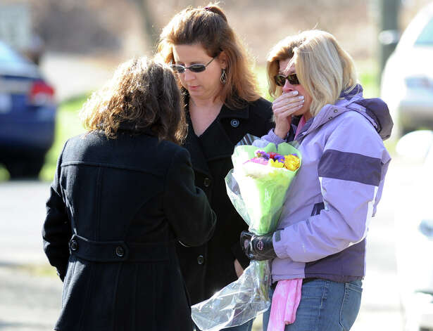 Mourners prepare to place flowers near the Sandy Hook Elementary School sign which is on the corner of Riverside Road and Dickenson Drive in Sandy Hook, Conn., Saturday, Dec. 15, 2012. Town resident Adam Lanza, 20, is suspected of killing 27 people at the school Friday morning. Photo: Bob Luckey / Greenwich Time