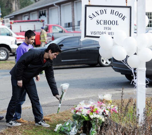 Mourners place flowers near the Sandy Hook Elementary School sign which is on the corner of Riverside Road and Dickenson Drive in Sandy Hook, Conn., Saturday, Dec. 15, 2012. Town resident Adam Lanza, 20, is suspected of killing 27 people at the school Friday morning. Photo: Bob Luckey / Greenwich Time