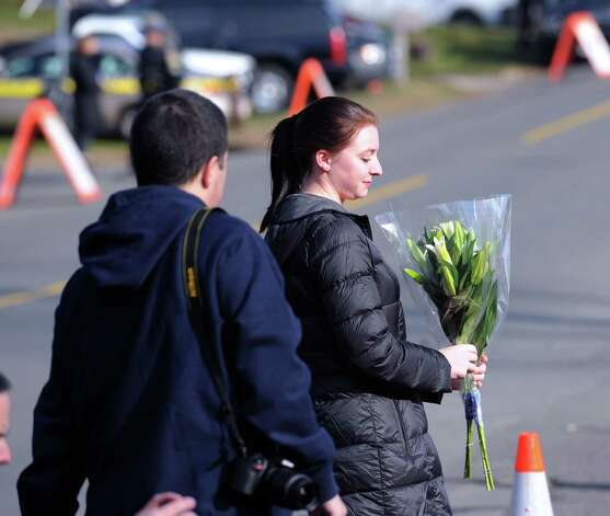 Jessica Henderson of Shelton, Conn., a Newtown High School graduate class of 2011, prepares to place flowers near the Sandy Hook Elementary School sign which is on the corner of Riverside Road and Dickenson Dri