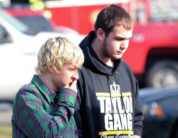 At left, Nicholas Clarke, 18, and Justin Cherry, 17, of Newtown, stand near the Sandy Hook Elementary School sign which is on the corner of Riverside Road and Dickenson Drive in Sandy Hook, Conn., Saturday, Dec. 15, 2012. Newtown resident Adam Lanza, 20, is suspected of killing 27 people at the school Friday morning. Photo: Bob Luckey / Greenwich Time