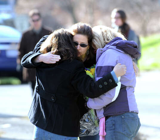 Mourners embrace near the Sandy Hook Elementary School sign which is on the corner of Riverside Road and Dickenson Drive in Sandy Hook, Conn., Saturday, Dec. 15, 2012. Town resident Adam Lanza, 20, is suspected of killing 27 people at the school Friday morning. Photo: Bob Luckey / Greenwich Time