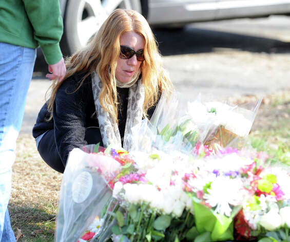 Amy Rothenbucher of Sandy Hook places flowers near the Sandy Hook Elementary School sign which is on the corner of Riverside Road and Dickenson Drive in Sandy Hook, Conn., Saturday, Dec. 15, 2012. Town resident Adam Lanza, 20, is suspected of killing 27 people at the school Friday morning. Photo: Bob Luckey / Greenwich Time