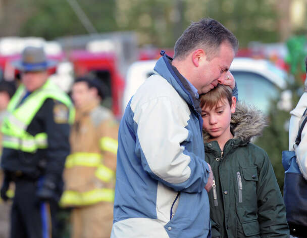 At left, Scott Lindsay of Newtown and his son, Christopher, 9, mourn near the Sandy Hook Elementary School sign which is on the corner of Riverside Road and Dickinson Drive in Sandy Hook, Conn., Saturday, Dec. 15, 2012. Christopher attends school in Newtown but is not a student at Sandy Hook Elementary School where town resident Adam Lanza, 20, is suspected of killing 27 people at the school Friday morning. Photo: Bob Luckey / Greenwich Time