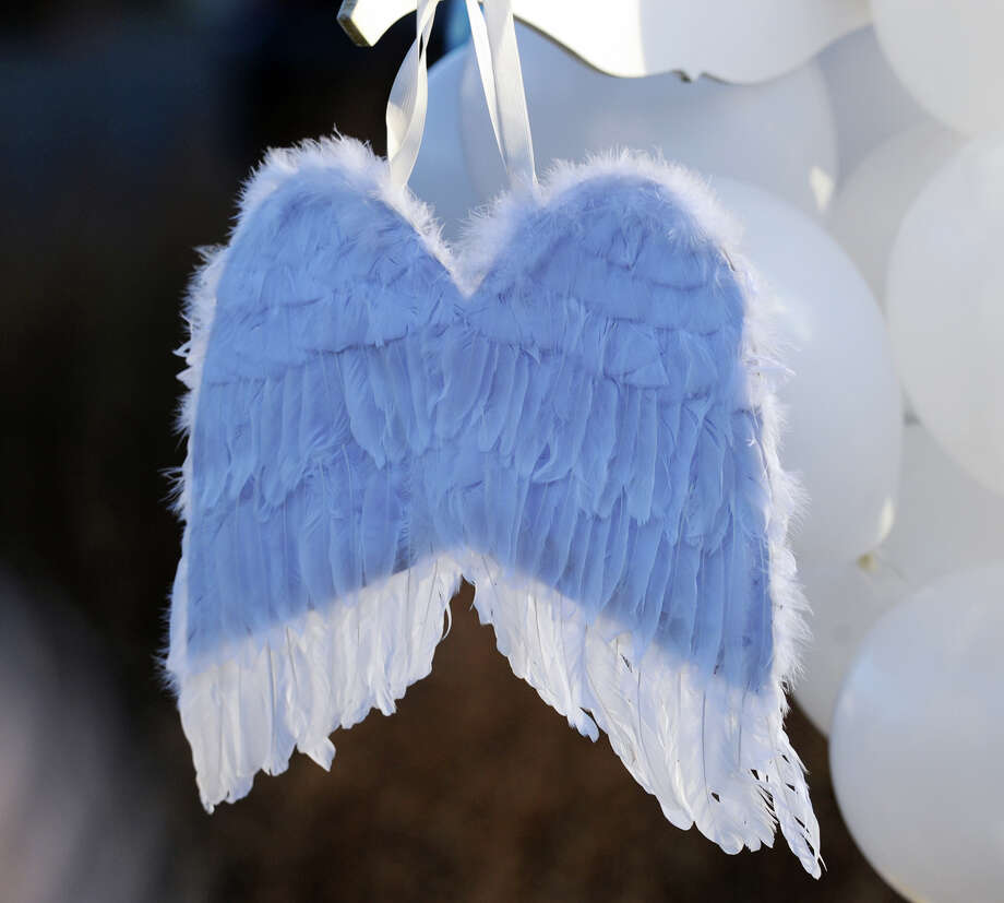 Angel's wings hang on the Sandy Hook Elementary School sign which is on the corner of Riverside Road and Dickinson Drive in Sandy Hook, Conn., Saturday, Dec. 15, 2012. Town resident Adam Lanza, 20, is suspected of killing 27 people at the school Friday morning. Photo: Bob Luckey / Greenwich Time