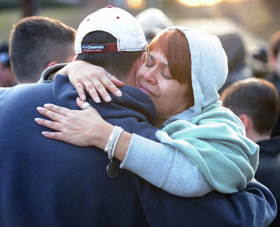 At right, Wendy Santos of Holyoke, Mass., hugs Carlos Reinos of Monroe, Conn., near the Sandy Hook Elementary School sign which is on the corner of Riverside Road and Dickinson Drive in Sandy Hook, Conn., Saturday, Dec. 15, 2012. Town resident Adam Lanza, 20, is suspected of killing 27 people at the school Friday morning. Photo: Bob Luckey / Greenwich Time