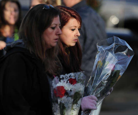 Mourners with flowers near the Sandy Hook Elementary School sign which is on the corner of Riverside Road and Dickinson Drive in Sandy Hook, Conn., Saturday, Dec. 15, 2012. Town resident Adam Lanza, 20, is suspected of killing 27 people at the school Friday morning. Photo: Bob Luckey / Greenwich Time