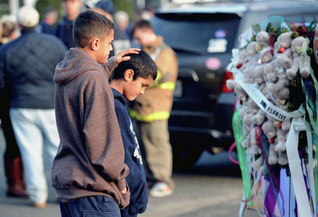 Brothers Thomas (left) and Steven Leuci, 13 and 9 of Newtown, mourn near the Sandy Hook Elementary School sign which is on the corner of Riverside Road and Dickinson Drive in Sandy Hook, Conn., Saturday, Dec. 15, 2012. Town resident Adam Lanza, 20, is suspected of killing 27 people at the school Friday morning. Photo: Bob Luckey / Greenwich Time