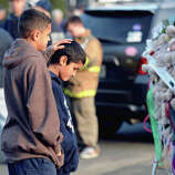 Brothers Thomas (left) and Steven Leuci, 13 and 9 of Newtown, mourn near the Sandy Hook Elementary School sign which is on the corner of Riverside Road and Dickinson Drive in Sandy Hook, Conn., Saturday, Dec. 15, 2012. Town resident Adam Lanza, 20, is suspected of killing 27 people at the school Friday morning.
