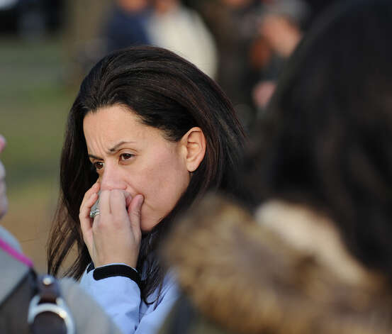 A woman who was crying speaks on a mobile phone near the Sandy Hook Elementary School sign which is on the corner of Riverside Road and Dickinson Drive in Sandy Hook, Conn., Saturday, Dec. 15, 2012. Town resident Adam Lanza, 20, is suspected of killing 27 people at the school Friday morning. Photo: Bob Luckey / Greenwich Time