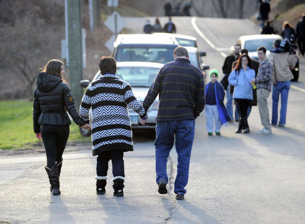 Three people hold hands as they walk near the Sandy Hook Elementary School sign which is on the corner of Riverside Road and Dickinson Drive in Sandy Hook, Conn., Saturday, Dec. 15, 2012. Town resident Adam Lanza, 20, is suspected of killing 27 people at the school Friday morning. Photo: Bob Luckey / Greenwich Time