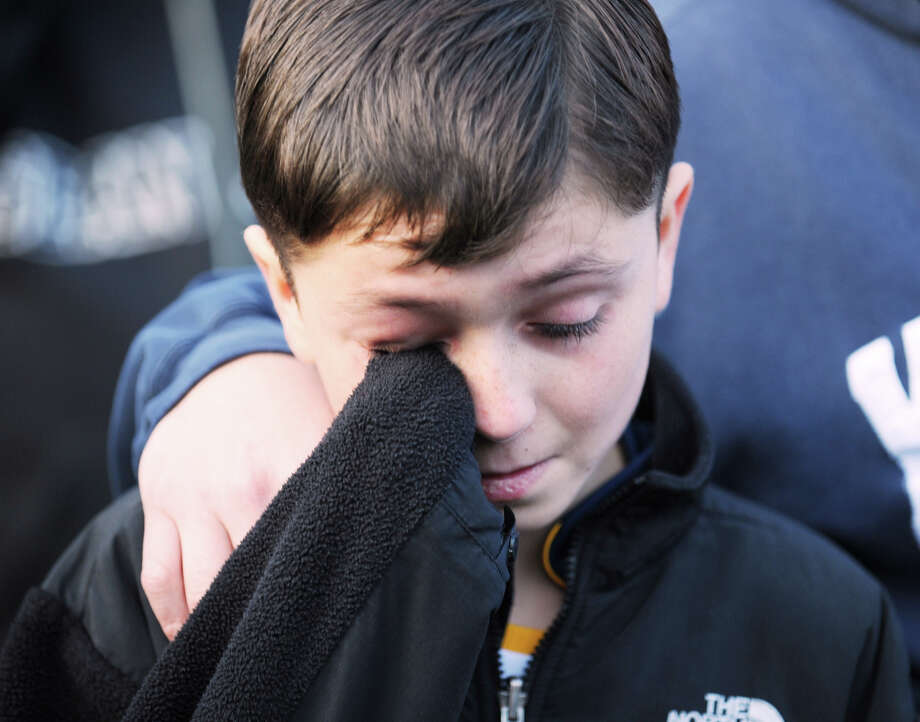 Jaime Reinos, 12, of Monroe, mourns near the Sandy Hook Elementary School sign which is on the corner of Riverside Road and Dickinson Drive in Sandy Hook, Conn., Saturday, Dec. 15, 2012. Town resident Adam Lanza, 20, is suspected of killing 27 people at the school Friday morning. Photo: Bob Luckey / Greenwich Time