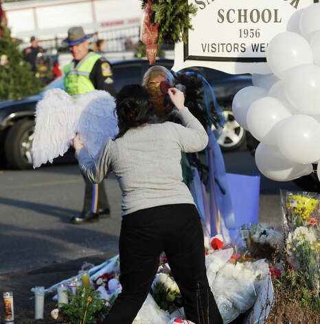 A woman hangs angel's wings on the Sandy Hook Elementary School sign which is on the corner of Riverside Road and Dickinson Drive in Sandy Hook, Conn., Saturday, Dec. 15, 2012. Town resident Adam Lanza, 20, is suspected of killing 27 people at the school Friday morning. Photo: Bob Luckey / Greenwich Time