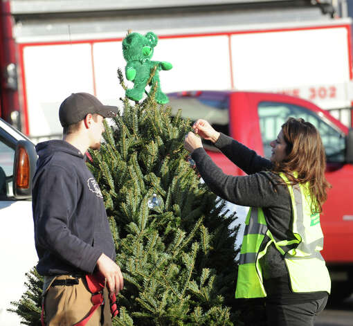 A woman decorates a Christmas tree in memory of the victims of the Sandy Hook Elementary School shootings, at the fire house on the corner of Riverside Road and Dickinson Drive in Sandy Hook, Conn., Saturday, Dec. 15, 2012. Town resident Adam Lanza, 20, is suspected of killing 27 people at the school Friday morning. Photo: Bob Luckey / Greenwich Time