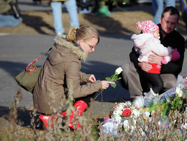 A mourner places a flower near the Sandy Hook Elementary School sign which is on the corner of Riverside Road and Dickinson Drive in Sandy Hook, Conn., Saturday, Dec. 15, 2012. Town resident Adam Lanza, 20, is suspected of killing 27 people at the school Friday morning. Photo: Bob Luckey / Greenwich Time
