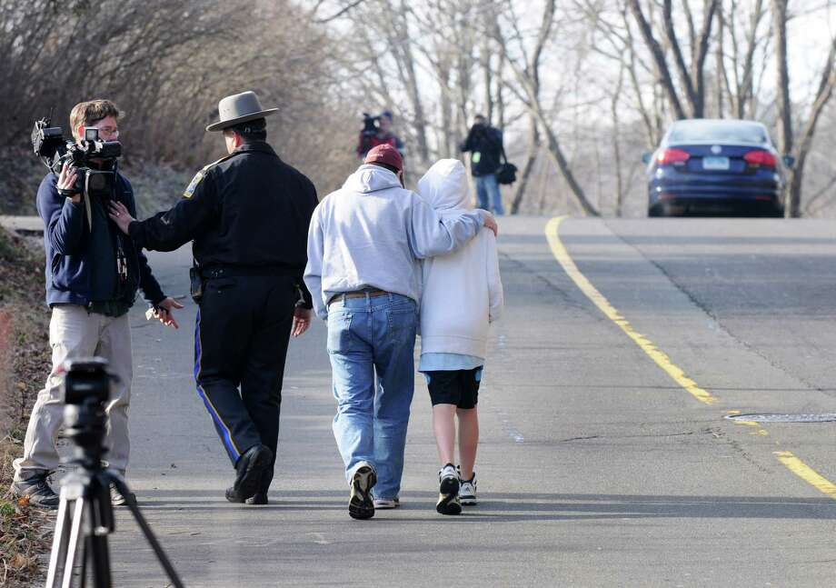 A cameraman is pushed aside as a sympathetic man accompanied by a young boy leaves Sandy Hook Elementary School after the pair placed flowers at the entrance to the school, Saturday Dec. 15, 2012, in Newtown, Conn. Twenty-seven people including 20 children were killed by a lone gunman yesterday at the school. Photo: Will Waldron, Hearst Connecticut Newspapers/Wi / The News-Times