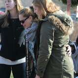 Support is given to a woman who came from out of town to pay her respects, Saturday, Dec. 15, 2012, to the victims of yesterday's tragic shooting at Sandy Hook Elementary School in Newtown, Conn.
