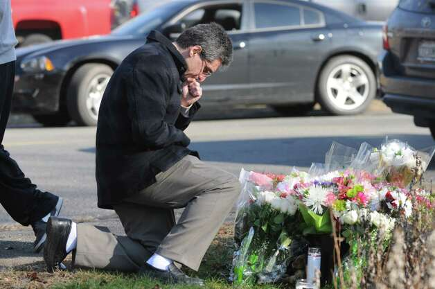 Alexander Glinski of Trumbull Conn. leaves flowers and a candles as he pays his respects outside the Sandy Hook Elementary School on Saturday, Dec. 15, 2012. Twenty children and six adults were killed yesterday at the school in Newtown, Conn. Photo: Will Waldron, Hearst Connecticut Newspapers/Wi / The News-Times