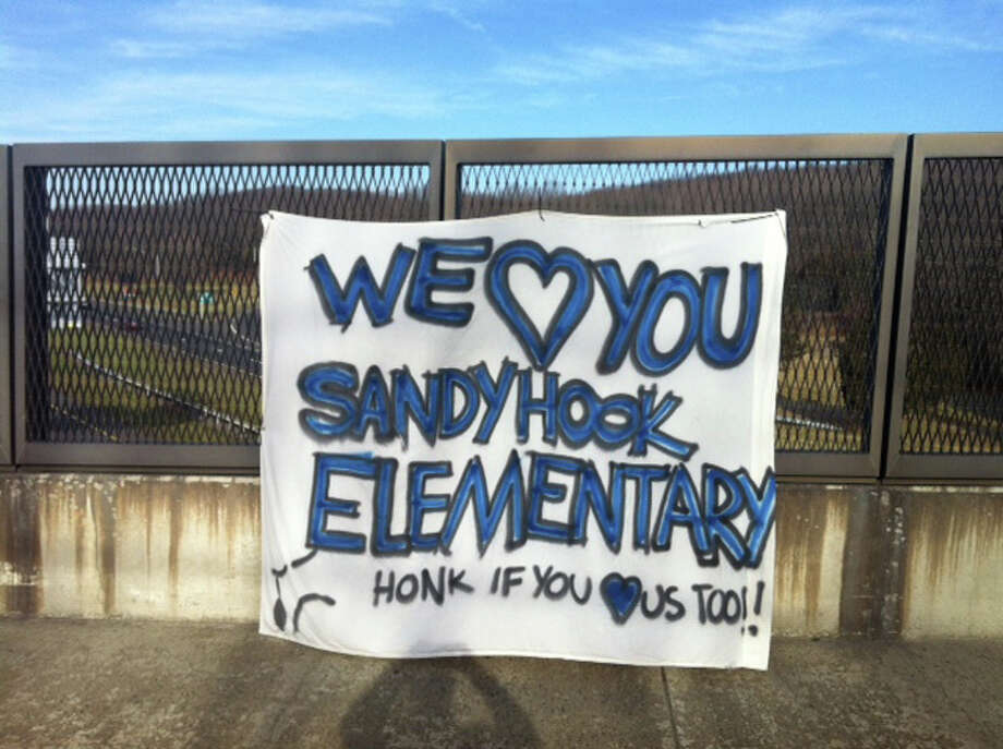 A sign just off the highway on Saturday, Dec. 15, 2012, shows support for the victim's of yesterday's horrific bloodbath at the Sandy Hook Elementary School in Newtown, Conn. where twenty-seven people including 20 children were massacred. Photo: Bob Luckey / Greenwich Time