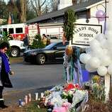 Mourners place flowers on a memorial built around the sign for the Sandy Hook School in Newtown Saturday, Dec. 15, 2012. Sandy Hook Elementary School was the site of a mass shooting on Friday.