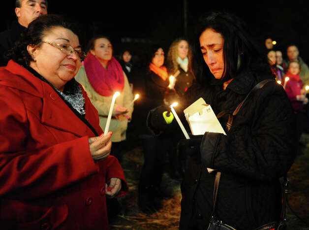 Fairfield teacher Jane Vigliotti, of Stratford, at right, lights extra candles she brought to hand out as hundreds attend a candlelight vigil in memory of victims from yesterday's mass shooting in Newtown, which was held behind Stratford High School on the Town Hall Green in Stratford, Conn. on Saturday December 15, 2012. At left is her friend and
